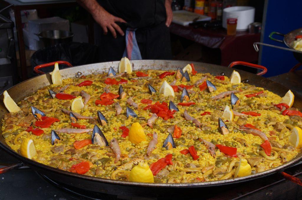 Paella Catering Köln - eine riesen Pfanne mit Paella Reis , Meeresfrüchten wie Gambas und Muscheln und Zitronen als Dekoration